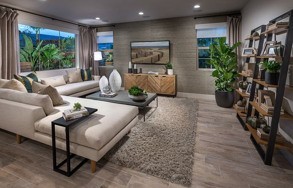 Plan 1 living room with sofa, area rug, wood floors, television, media cabinet, and large window