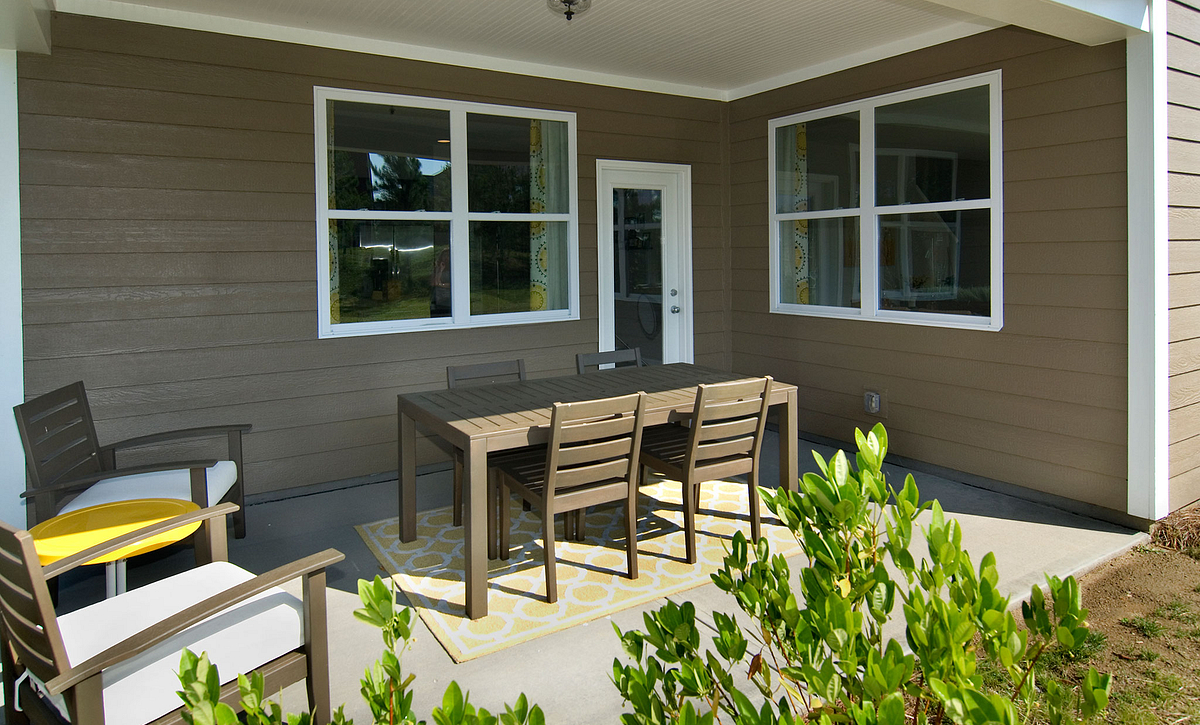 Covered rear porch with conversation area and dining table with chairs