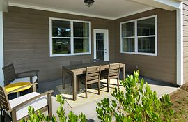 Rear covered porch with conversation area and dining table with chairs