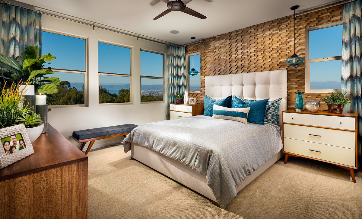 Plan 2 master bedroom with bed, ceiling fan, dresser, end tables, and pendant lights