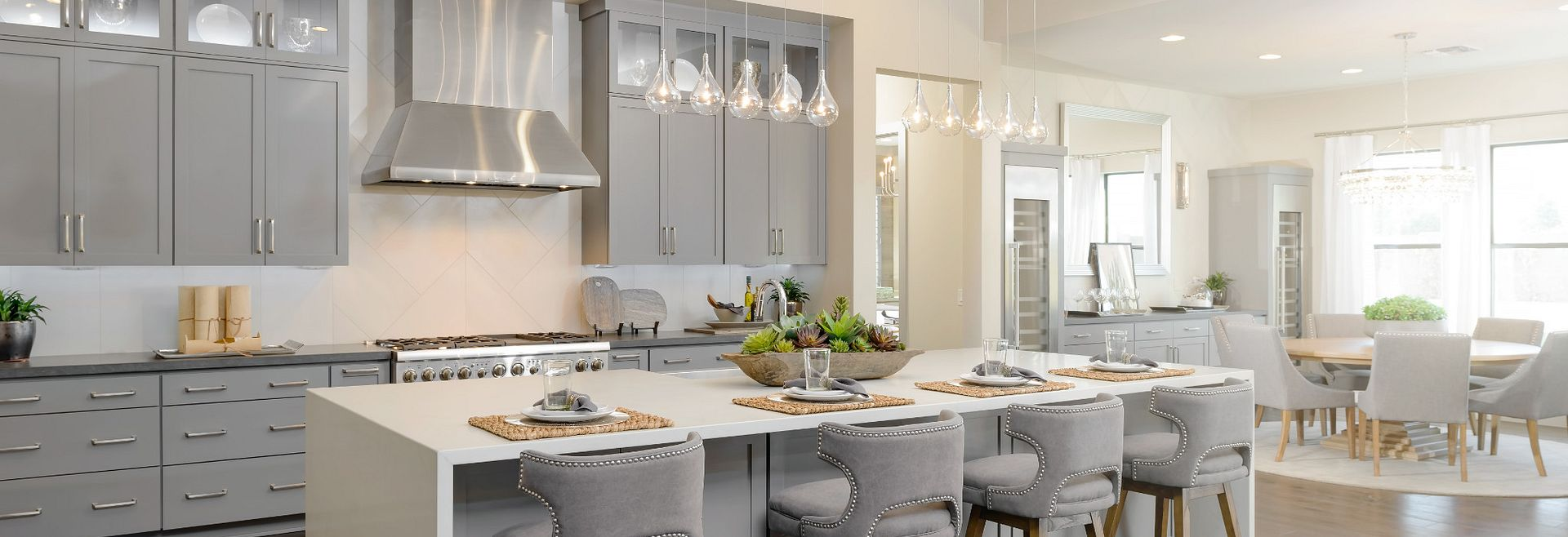 The Reserves Residence 4 Kitchen with grey cabinets, island seating, and eat-in area