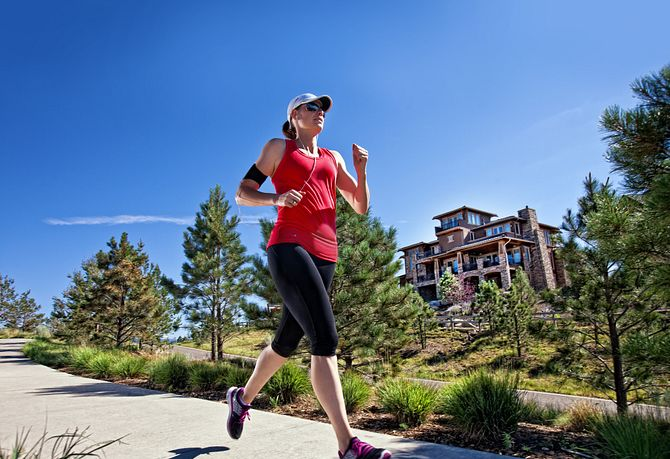 Woman running on paved trail through community