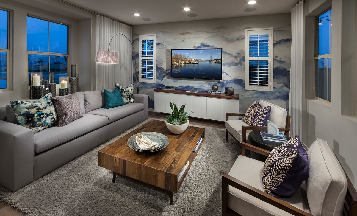 Plan 3 living room with coffee table, sofa, area rug, wood floors, recessed lights, and two club chairs