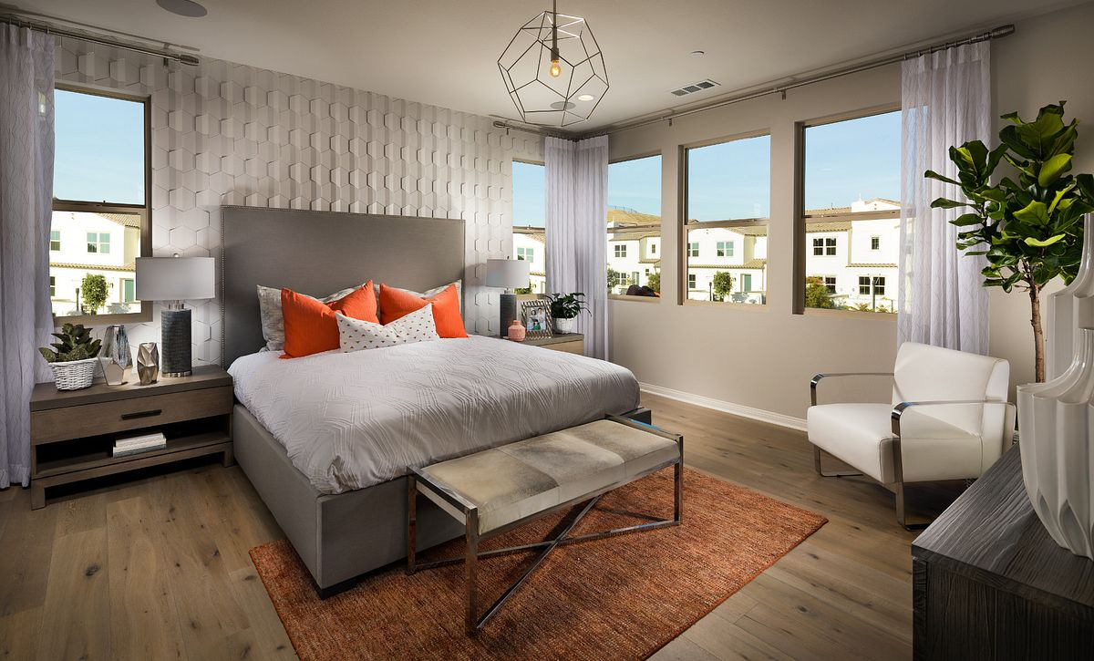 Plan 1 master bedroom with bed chandelier, night stands, table lamps, recessed lights, and wood floors