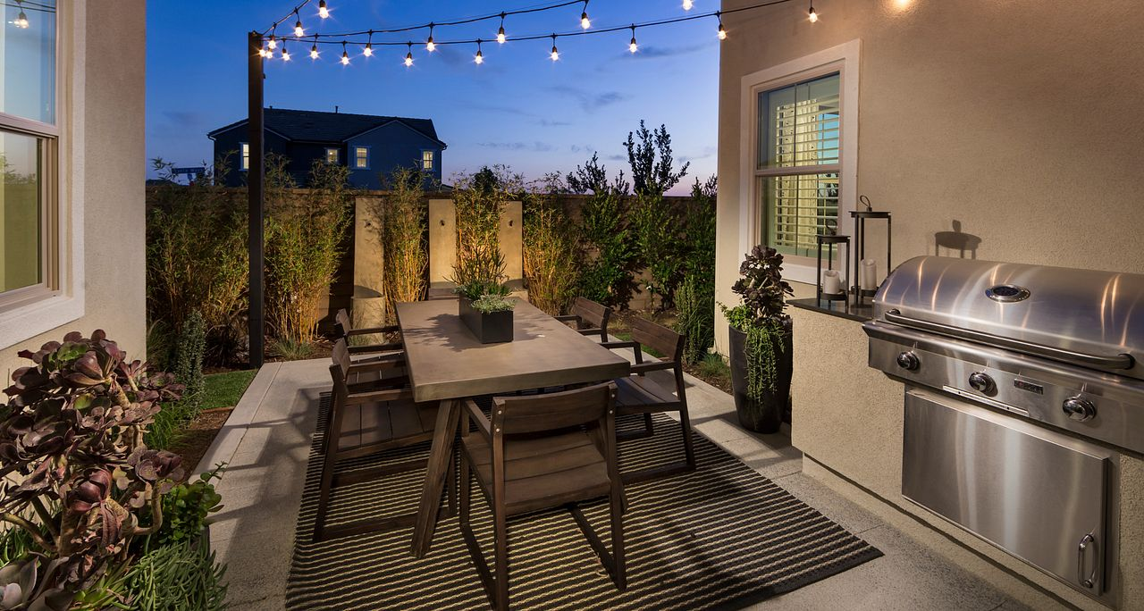 Plan 3 patio with string lights, barbecue, outdoor furniture, and grass
