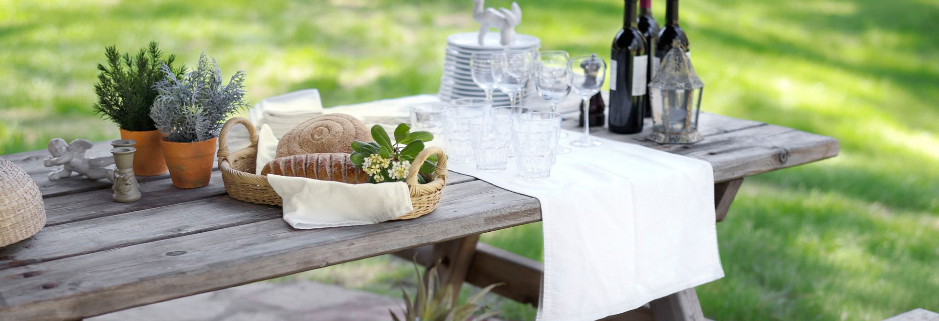 Picnic with table, basket of fruits, vegetables, and drinks