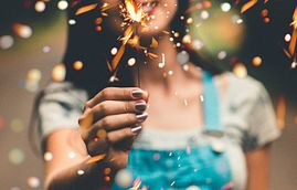 Woman holding a sparkler for a 4th of July celebration