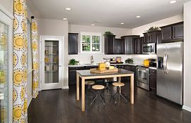 Kitchen with dark cabinets and floors and raised table with bar stools