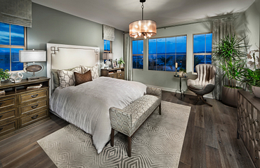 Plan 3 master bedroom with bed, chandelier, night stands, table lamps, dressing bench, and area rug