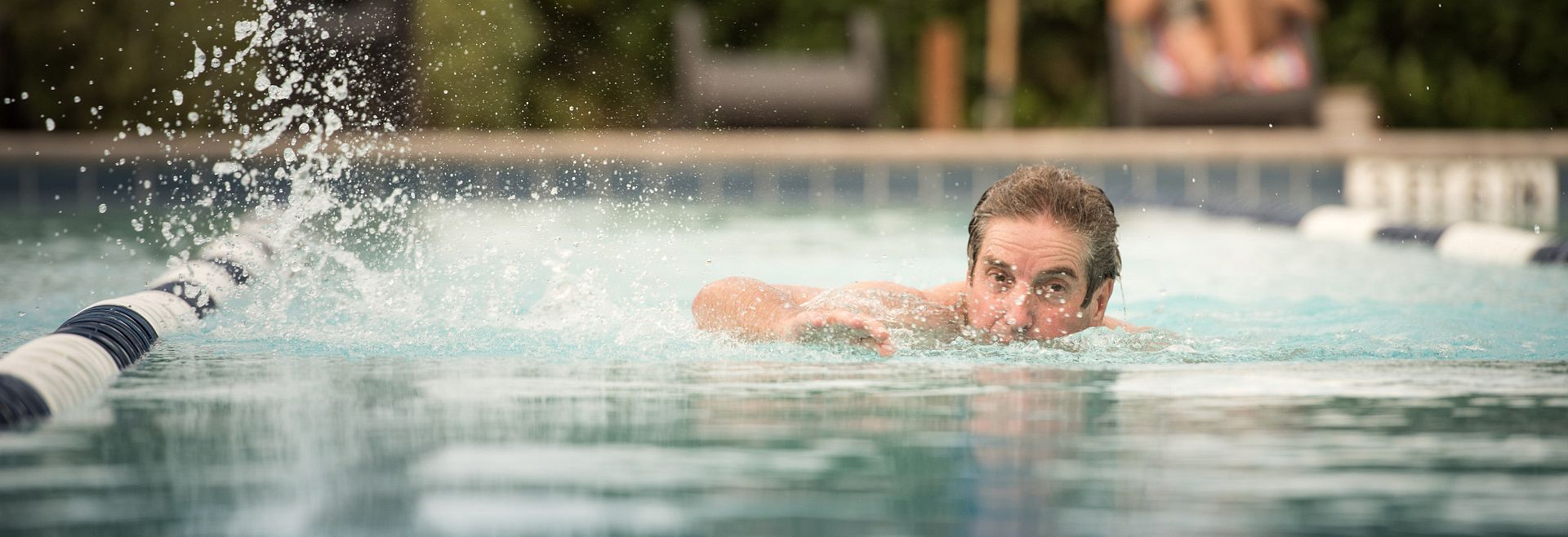 Man swimming in outdoor pool