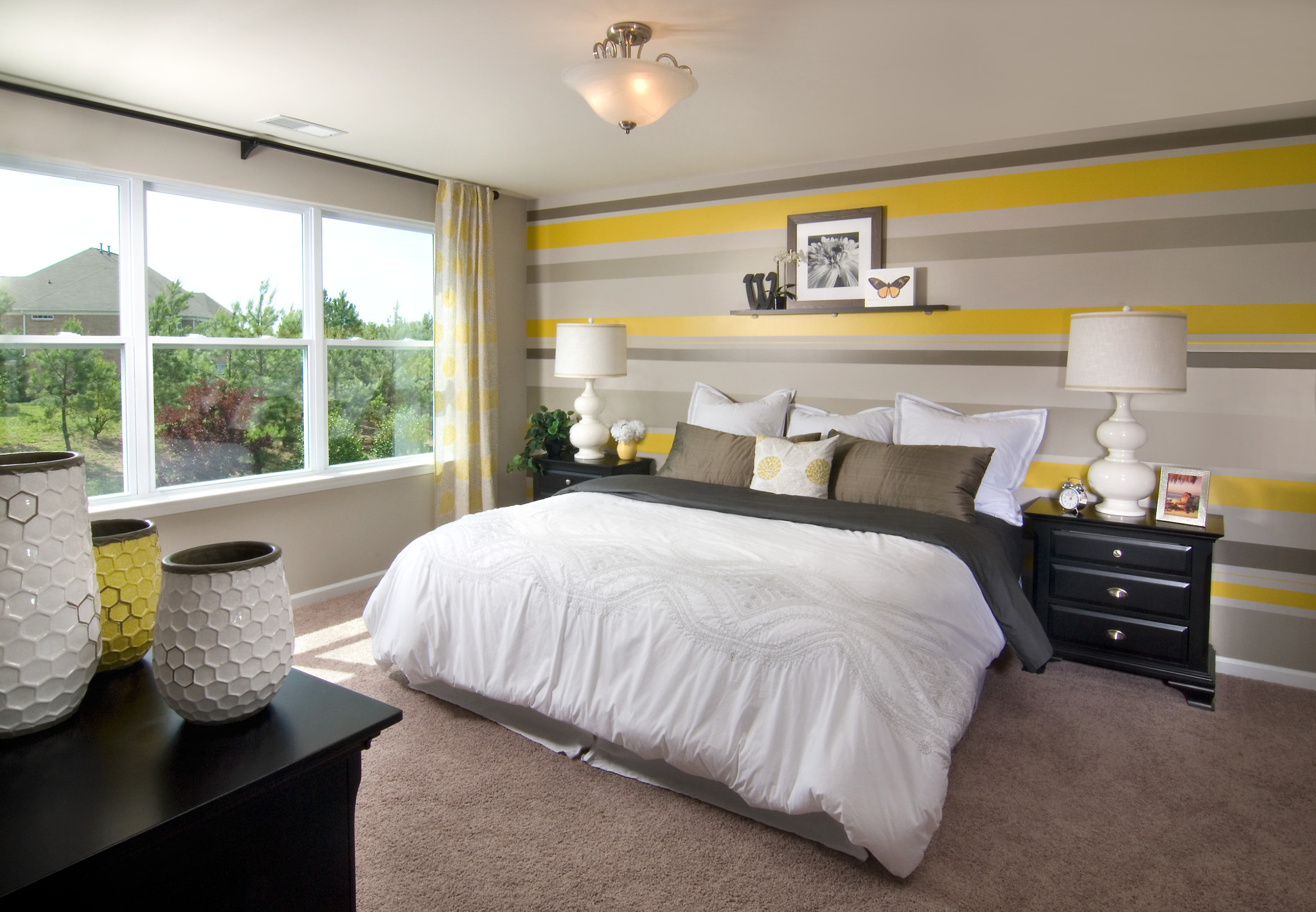 Master bedroom with yellow and gray accents and king sized bed