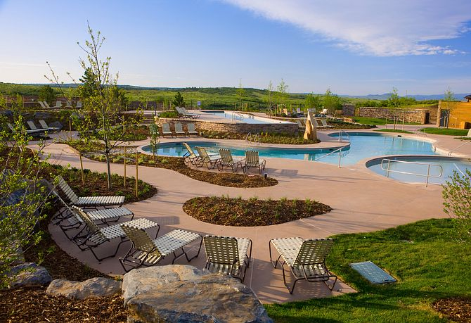 Pools and hot tubs with surrounding grass and lounge chairs at The Sundial House