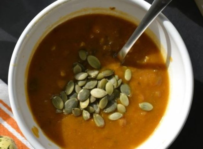 Pumpkin soup in a bowl sprinkled with pumpkin seeds
