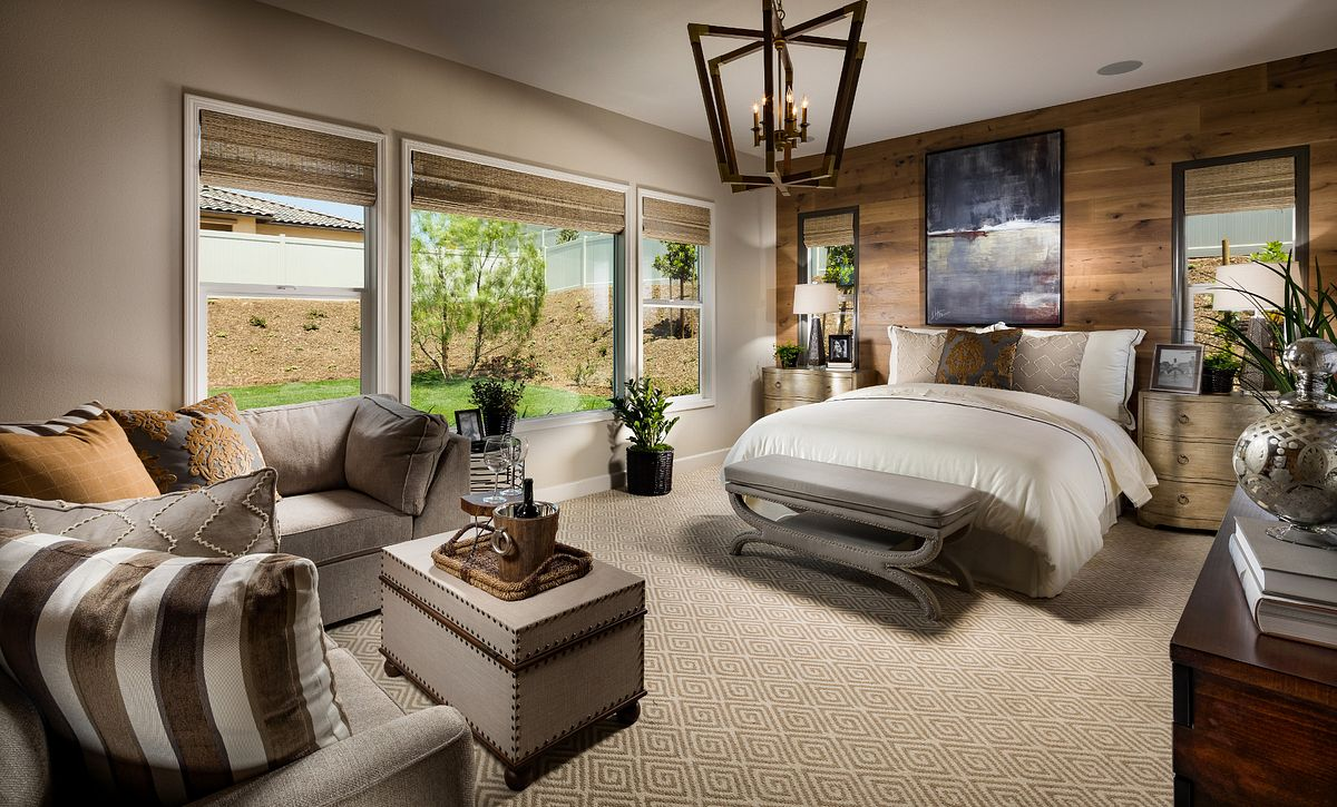 Plan 2 master bedroom with bed, chandelier, sofa, three windows, and dressing bench