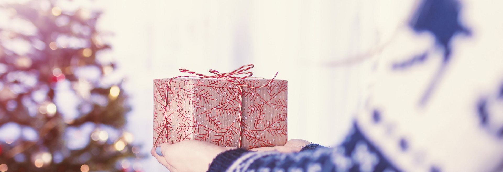 Woman holding out wrapped Christmas present