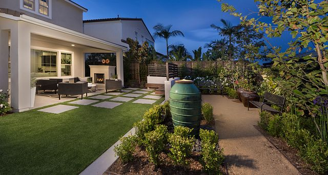 Plan 2 backyard with grass, fountain, and patio with outdoor furniture