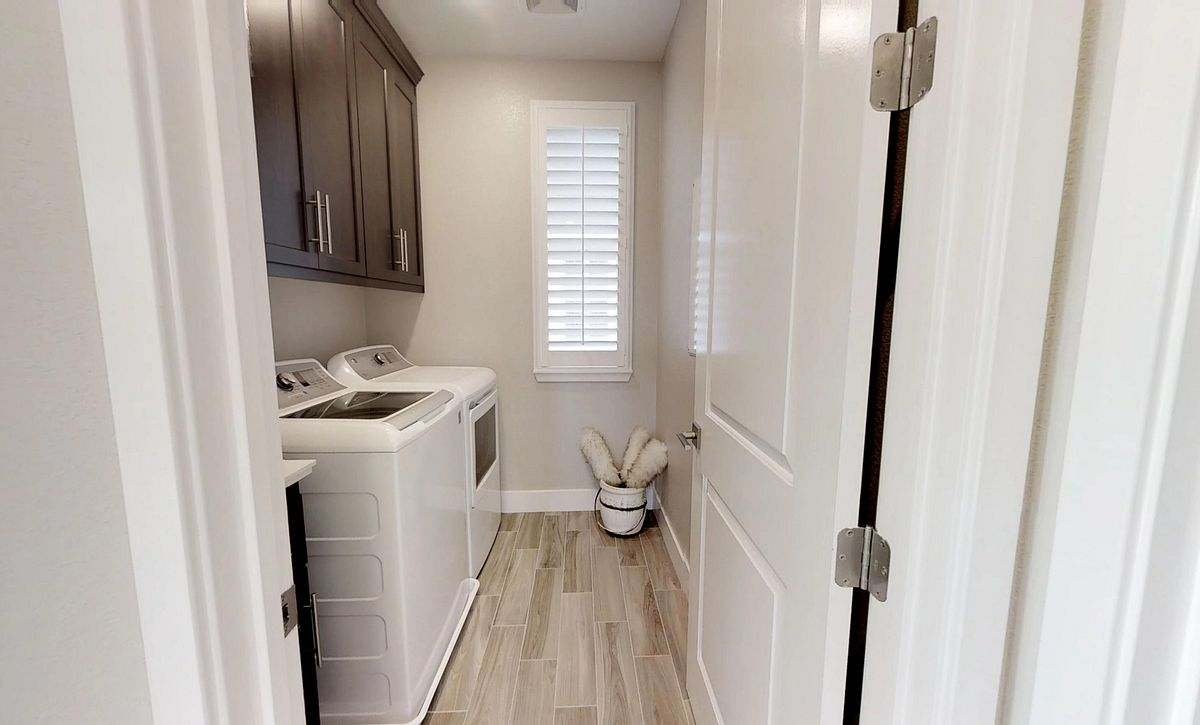 Plan 1 laundry room with washer and dryer, overhead cabinets, and wood floors