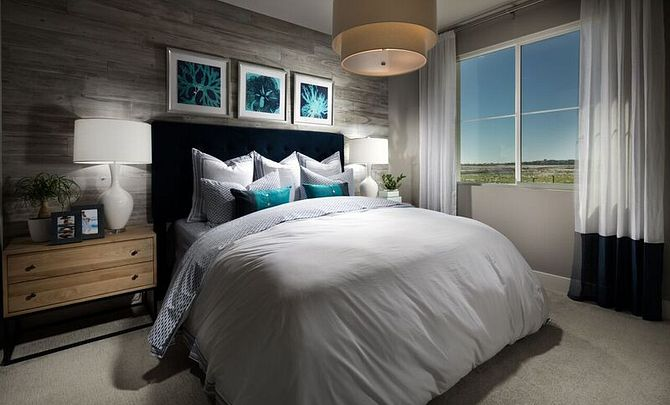 Plan 2 master bedroom with bed, chandelier, night stands, table lamps, and hanging pictures