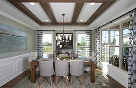 Dining room with tray ceiling and dark wood beams