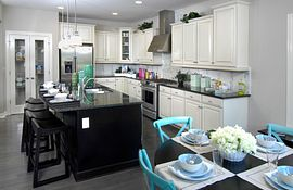 Kitchen with white cabinets and black island and granite counters