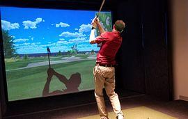 Man golfing in a golf simulator
