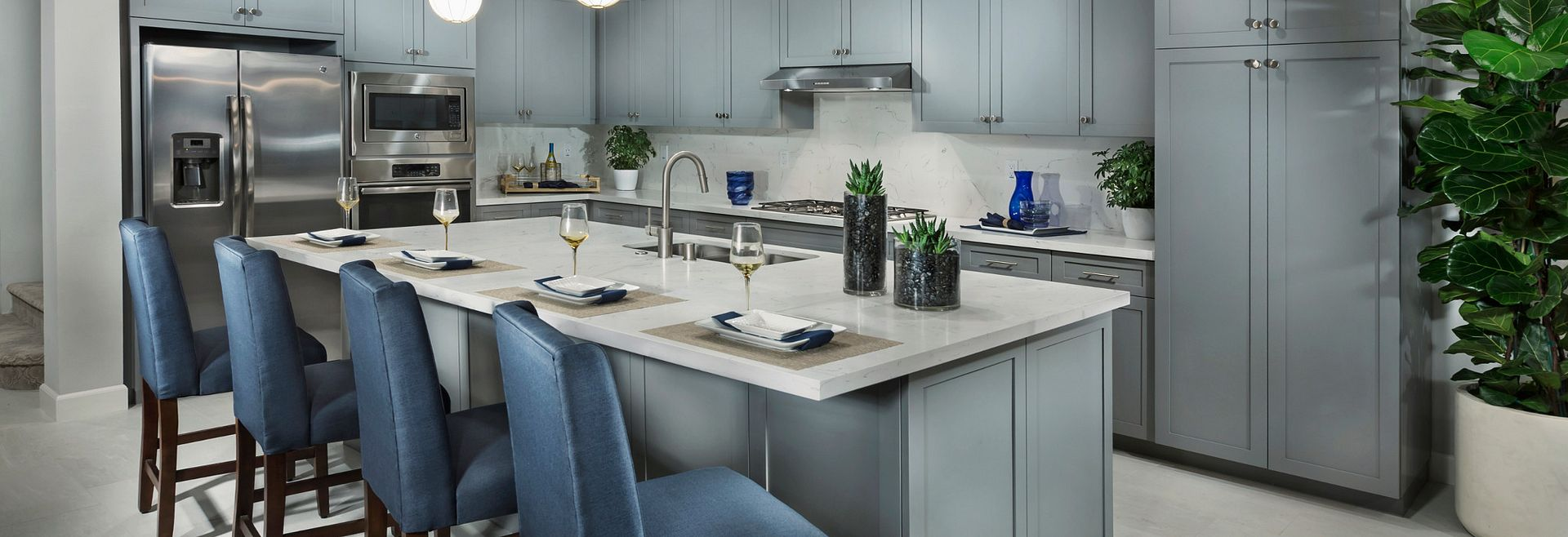 Plan 1 kitchen with center island, counter chairs, pendant lights, cabinets, and stainless steel appliances