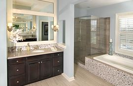 Master bath with dark cabinets, large tub and tiled shower