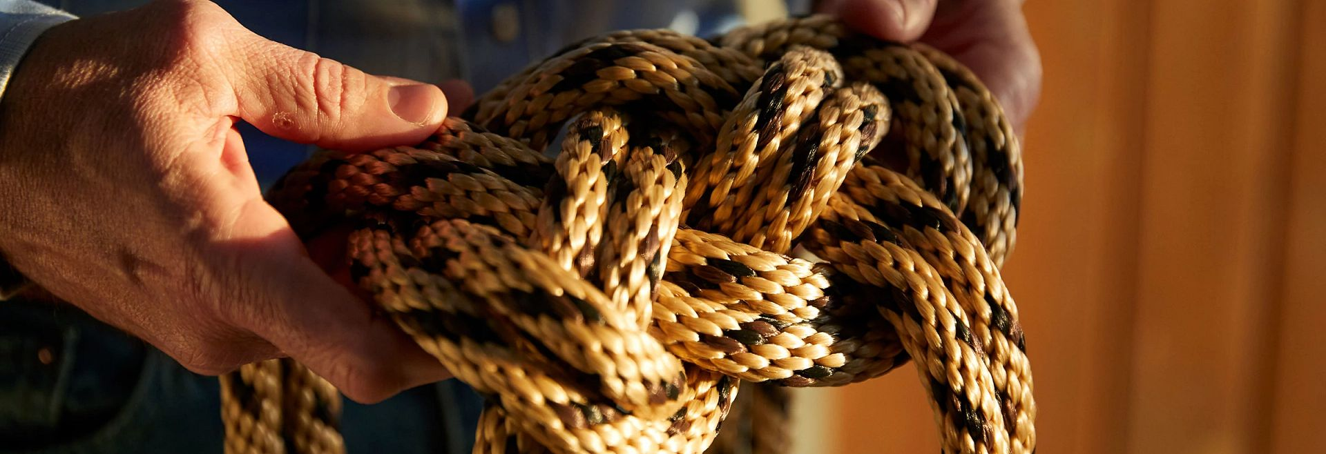 Man's Hands Holding a Knotted Rope