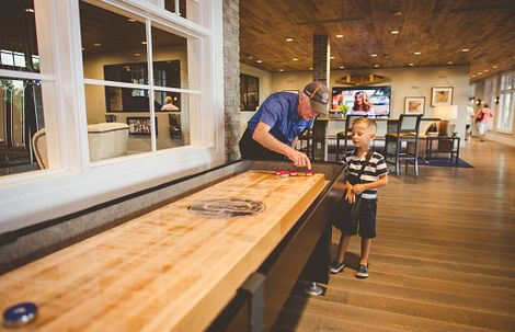 Grandpa showing grandkid how to play shuffleboard