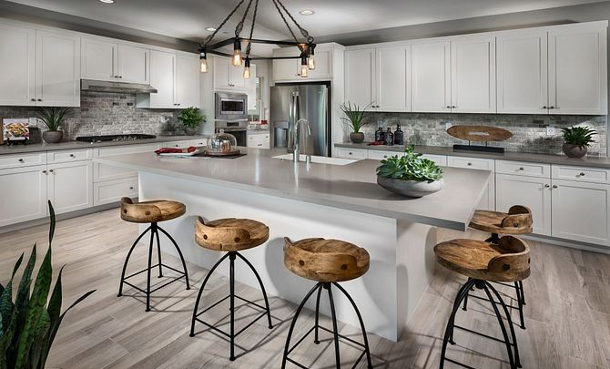 Plan 2 kitchen with center island, counter stools, chandelier, white cabinets, and stainless steel appliances