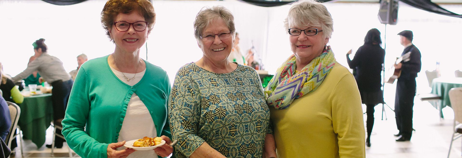 Women standing together, smiling, and enjoying food.