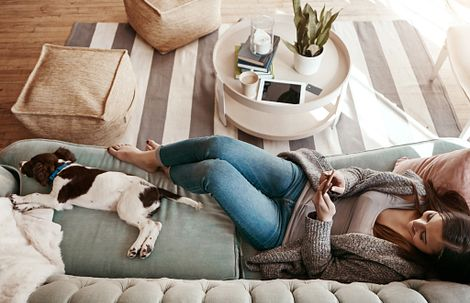 woman relaxing with dog on couch