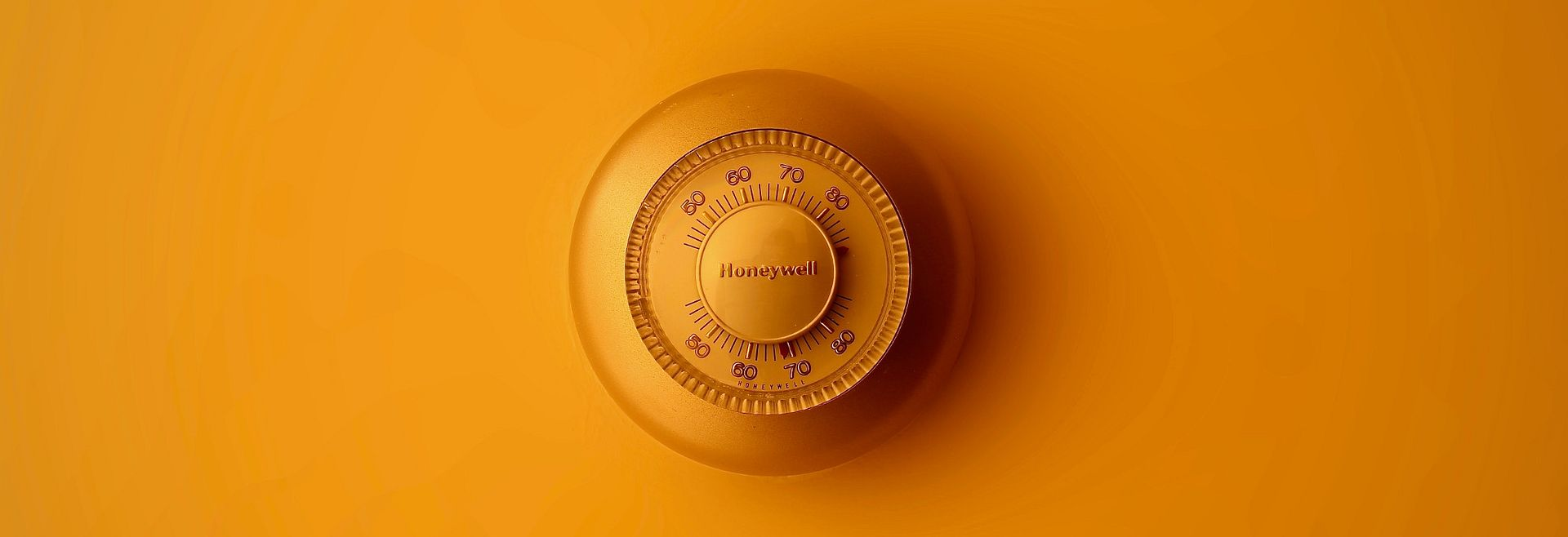 Orange Honeywell thermostat against orange wall