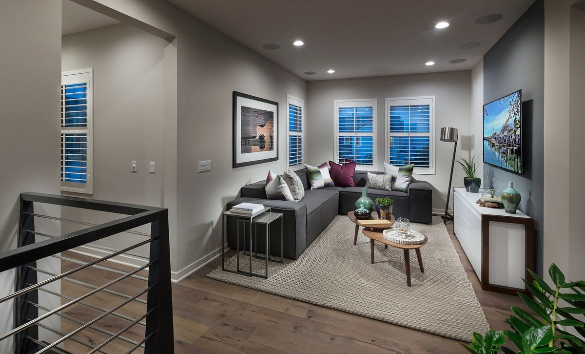 Plan 3 loft with sofa, coffee table, recessed lights, television, and media cabinet