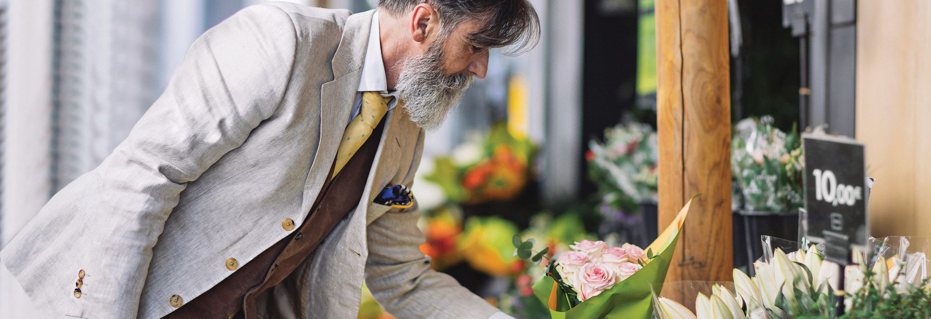 Man leaning over to choose a bouquet of flowers