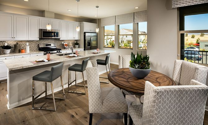 Plan 1 kitchen with center island, counter chairs, stainless steel appliances, pendant lights, and wood floors