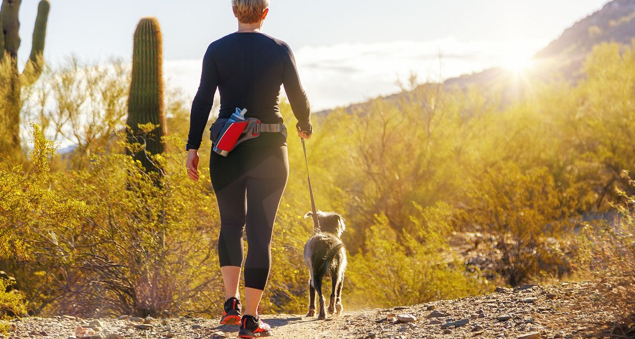 Woman walking dog on an Arizona desert trail