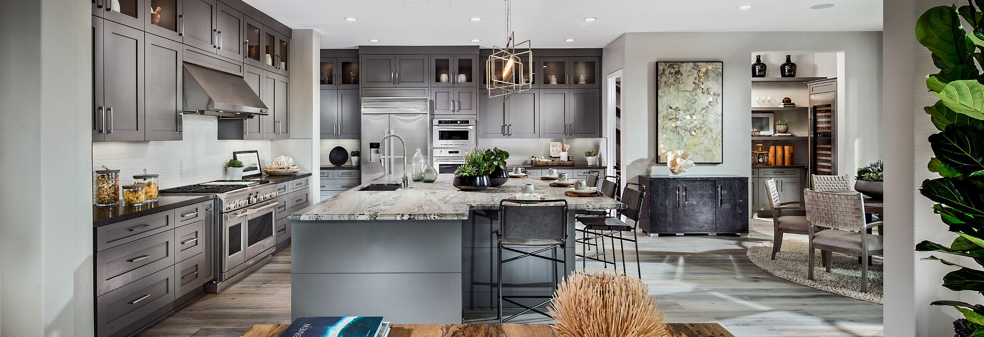 Residence 3 expansive kitchen with huge island that allows for bar stool seating, extended height grey cabinets, stainless steel appliances, recessed lighting, and pendant lighting