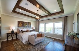Master bedroom with tray ceiling and wooden beams plus hardwood floors