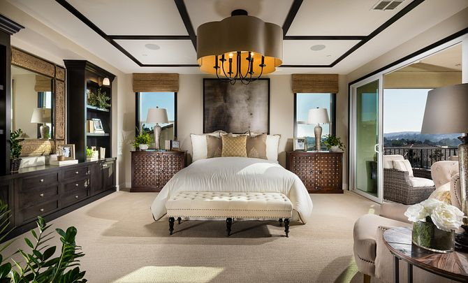 Plan 4 master bedroom with bed, chandelier, night stands with table lamps, dresser, and windows