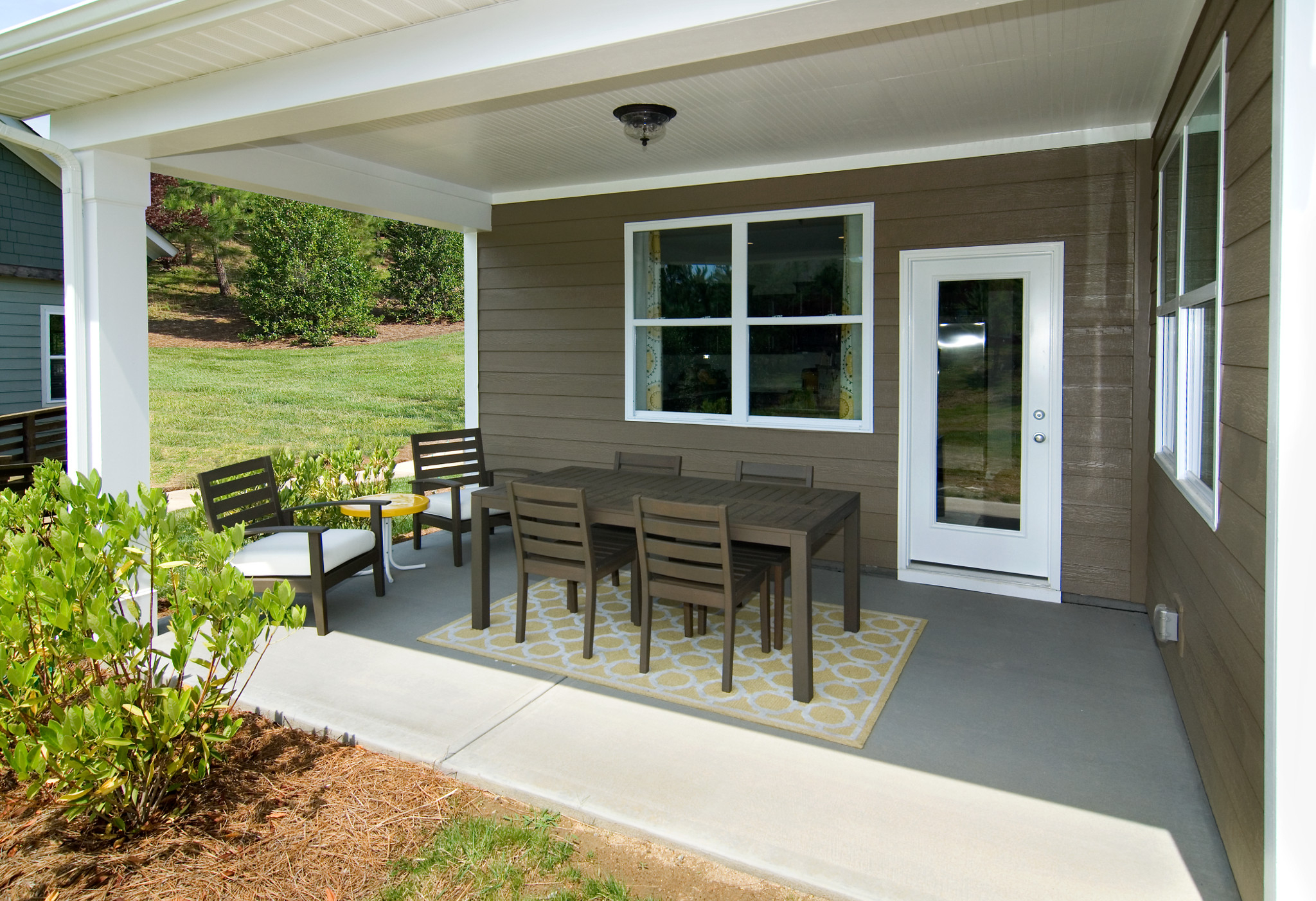 covered porch with dining table and conversation chairs