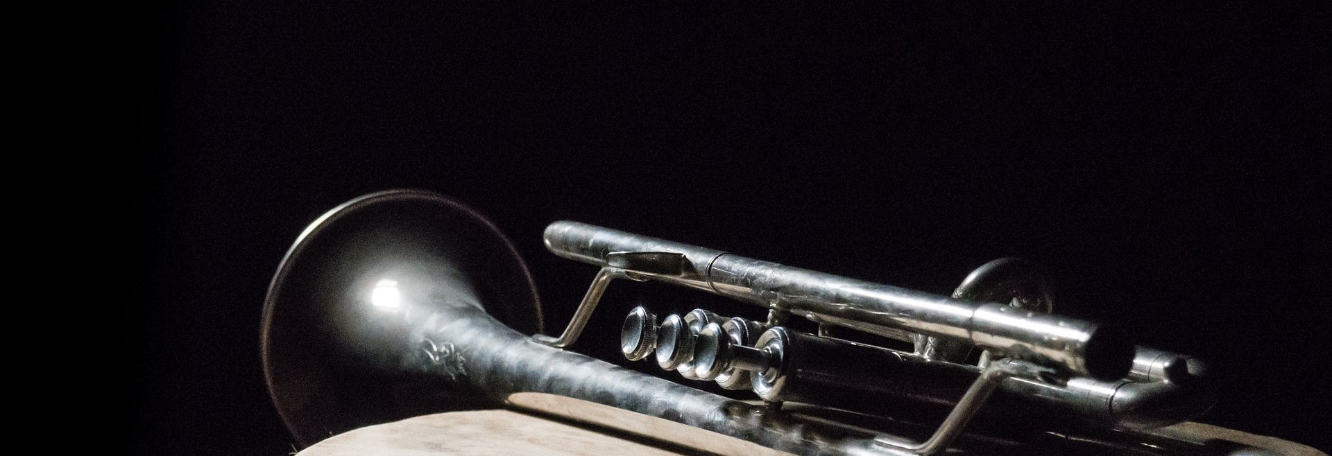 Trumpet laying on a stand against a black background