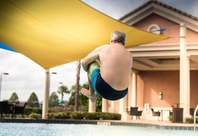 Man jumping into an outdoor pool