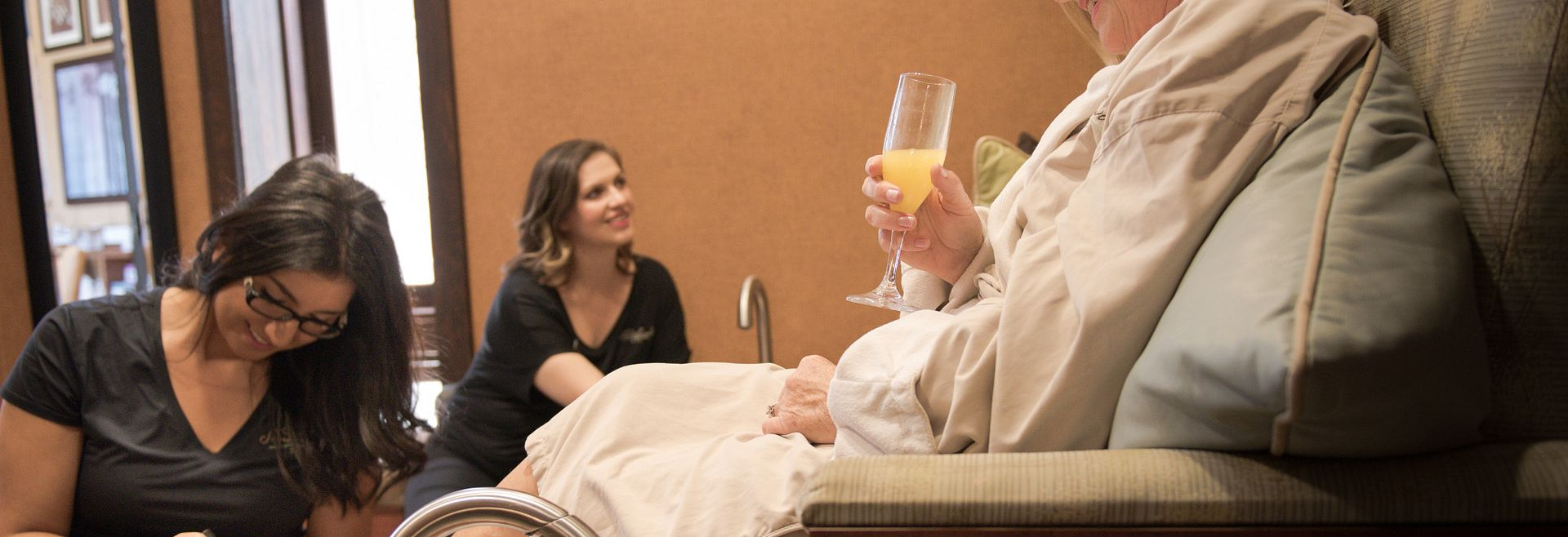 Woman in spa robe, holding beverage, and getting a pedicure