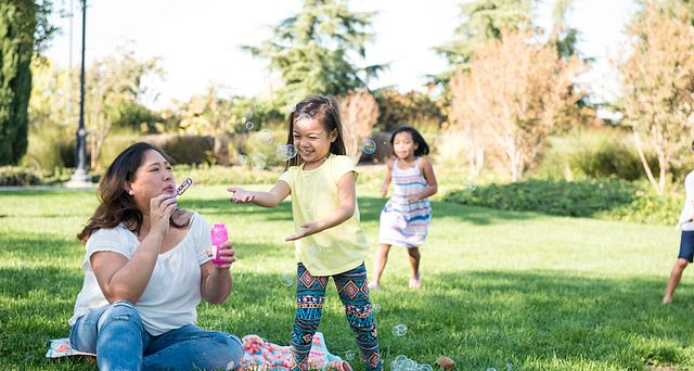 Mom and Girls Kids Play Bubbles at the Park
