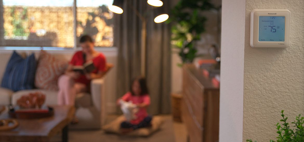 woman and child reading in the living room. Smart thermostat on the wall in front of them