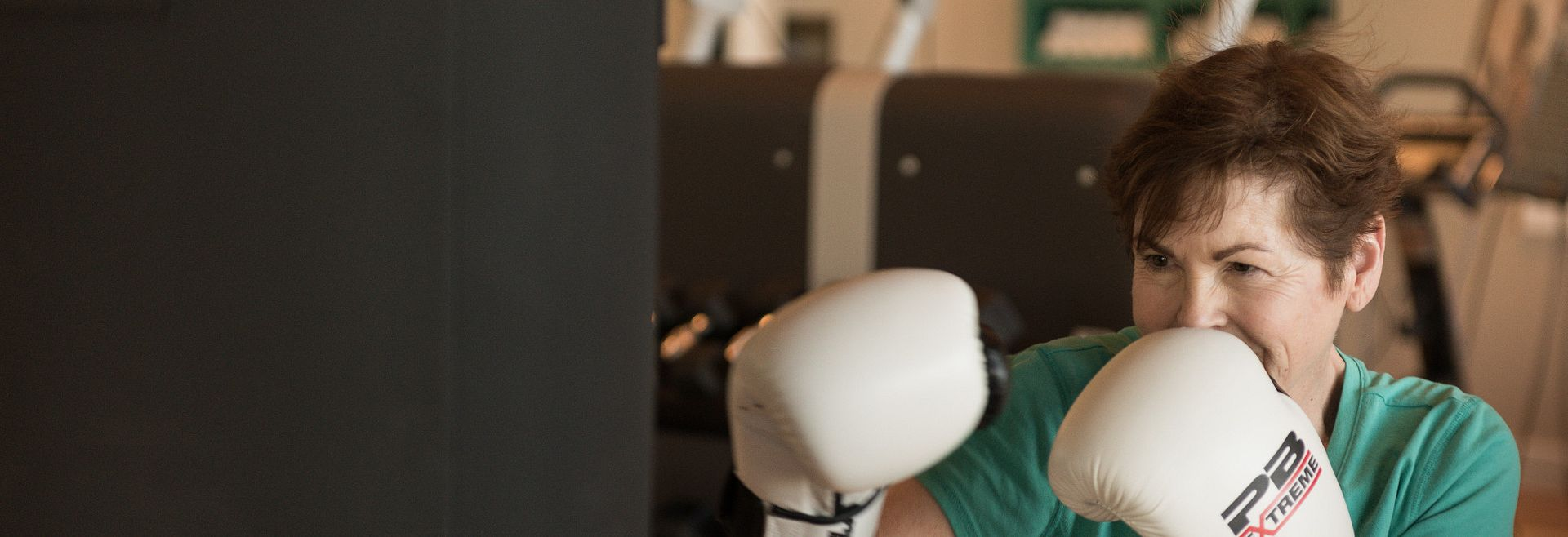 Woman wearing boxing gloves with punching bag