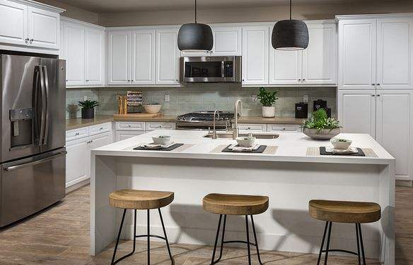 Plan 1 kitchen with center island, pendant lights, stainless steel appliances, white cabinets, and counter stools