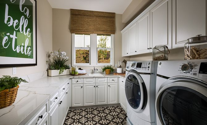 Plan 1 laundry room with washer, dryer, upper and lower cabinets
