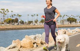 woman jogging with dog by the water